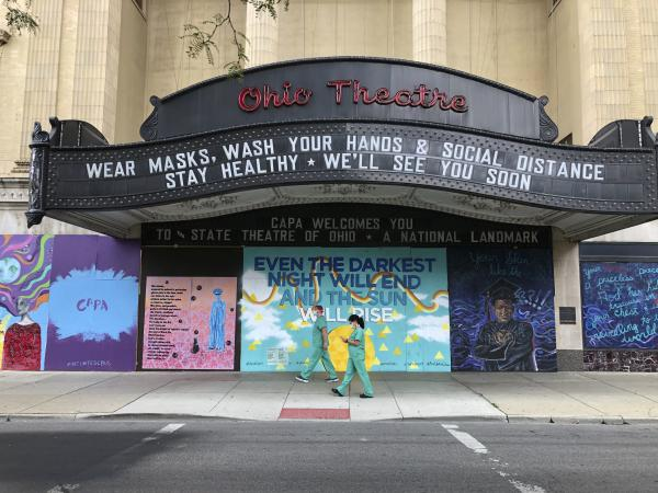 Workers in scrubs and masks walk past the Ohio Theatre in Columbus, Ohio last month amid the coronavirus pandemic.