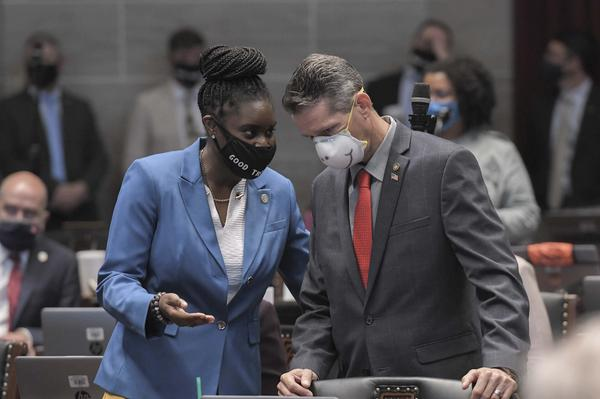 State Reps. LaKeySha Bosley, D-St. Louis, and Ron Hicks, R-Dardenne Prairie, talk on the House floor as lawmakers worked on approving crime bills during the special legislative session.