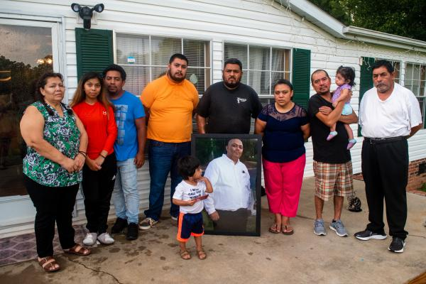 Members of the Chagoyan family stand outside their home in Midland, North Carolina, holding a portrait of Juan Chagoyan, who died July 20.