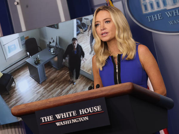 White House press secretary Kayleigh McEnany holds a briefing Thursday as a video of House Speaker Nancy Pelosi entering a San Francisco hair salon plays in the background.