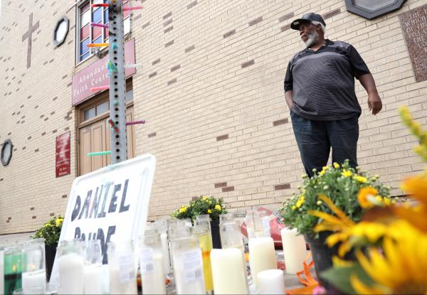 Pastor Arthur Dilbert stands in front of his church near a memorial for Daniel Prude