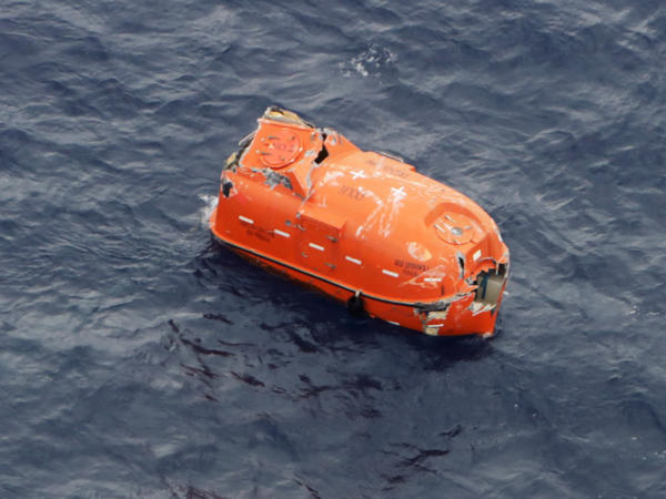 An unoccupied lifeboat drifts near Kodakarajima island. Japanese authorities are racing to find dozens of missing sailors from a cargo ship that sank in a typhoon.