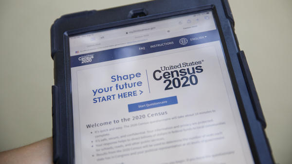 A volunteer in Los Angeles holds a computer tablet displaying the online questionnaire for the 2020 census in August.