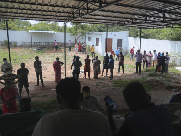 People wait in a queue to register their names before giving their nasal swab samples to test for COVID-19 at a government health center in Hyderabad, India on Saturday. India's coronavirus cases have crossed 4 million.