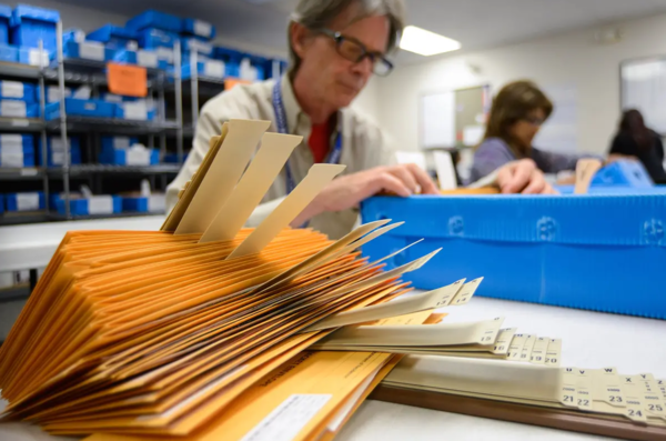 A clerk in Travis County goes through mail-in ballot packages in Travis County in 2014.
