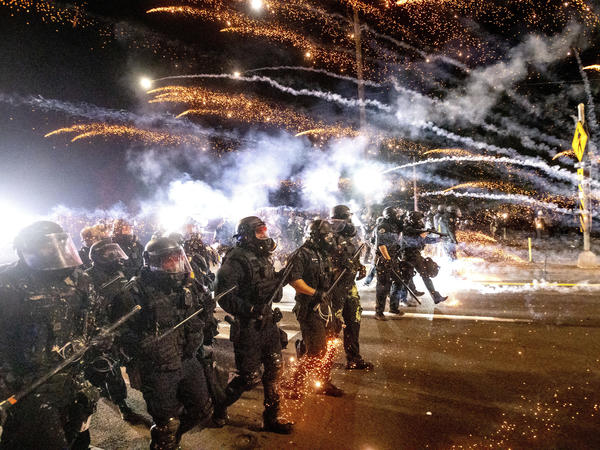 "Police in riot gear unleashed a volley of tear gas and flash-bang grenades on the protesters after police say some lobbed ""multiple fire bombs, mortars, rocks and other items"" at officers on Saturday night."