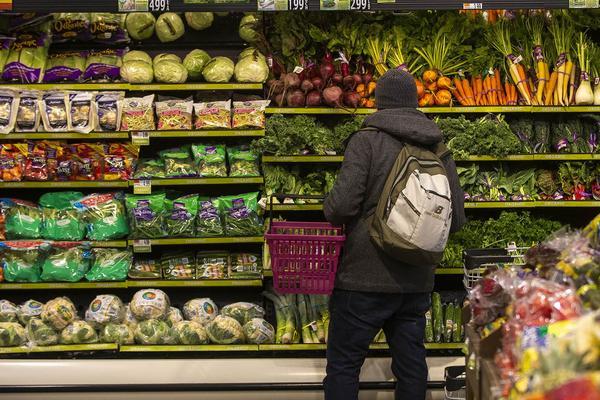 A customer peruses the produce at Roche Bros. in West Roxbury. (Jesse Costa/WBUR)