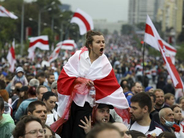 A woman covered in a red and white flag is among protesters in Minsk on Sept. 6. Sunday's demonstration marked the beginning of the fifth week of daily protests calling for Belarusian President Alexander Lukashenko's resignation.