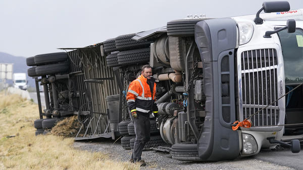 A semi rests in its side after after high winds toppled it on Interstate 15 near Bountiful, Utah, Tuesday.