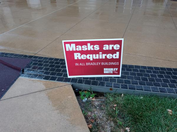 Mask requirement signs are posted across the Bradley University campus. This one is near the Hayden-Clark Alumni Center.