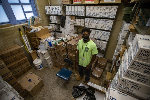 Custodian Earnest Bass stands in the storage room filled with cleaning supplies at the McCormack School in Dorchester. (Jesse Costa/WBUR)