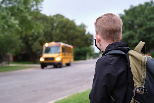 A First Student school bus in Wichita pulls up to pick up a waiting student.