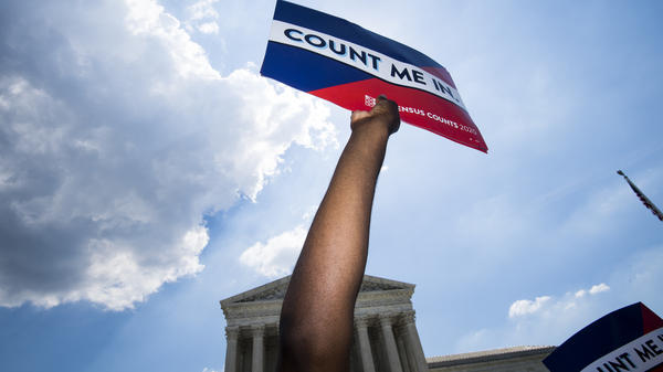 Protesters hold signs about the 2020 census at a rally in front of the Supreme Court in 2019.