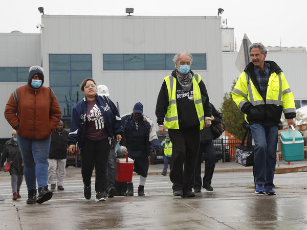 United Auto Workers members leave the Fiat Chrysler Automobiles Warren Truck Plant after a shift on May 18, 2020, in Warren, Mich. Car sales are picking up again, but auto makers face a problem: getting enough workers.