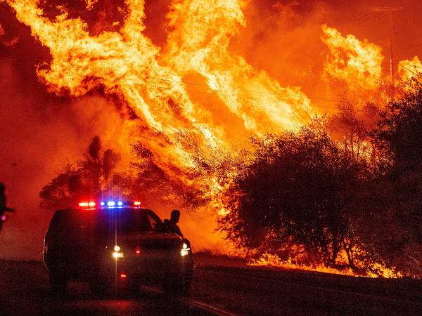 A law enforcement officer watches flames launch into the air as fire continues to spread during the Bear fire in Oroville, Calif. on September 9.