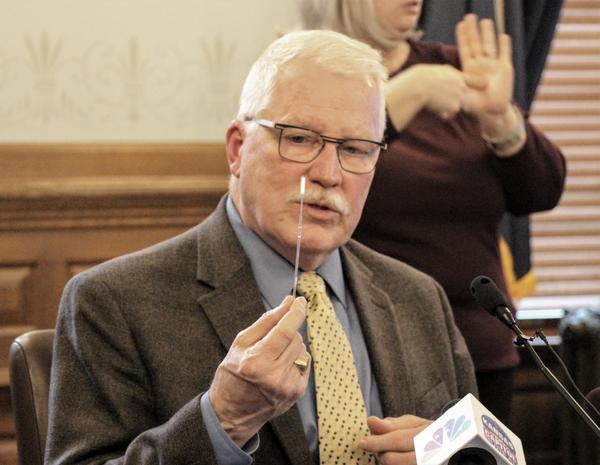 Kansas Health Secretary Lee Norman displays a swab used for COVID-19 testing. A small hospital in central Kansas has deployed blood tests that state health officials say can produce false positives among people with common colds.