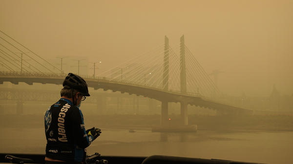 A man stops on his bike Saturday along the Willamette River as smoke from wildfires partially obscures the Tilikum Crossing Bridge in Portland, Ore.