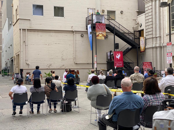 Father Michael O'Reilly preaches from a third-floor fire escape in a Sacramento alley while indoor worship services are prohibited due to COVID-19 heath restrictions.