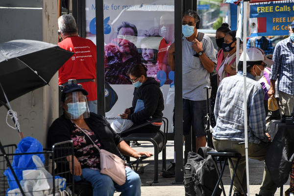People wait for a bus in August in East Los Angeles. Latinos have the highest rate of labor force participation of any group in California — many in public-facing jobs deemed essential. That work has put them at higher risk of catching the coronavirus.