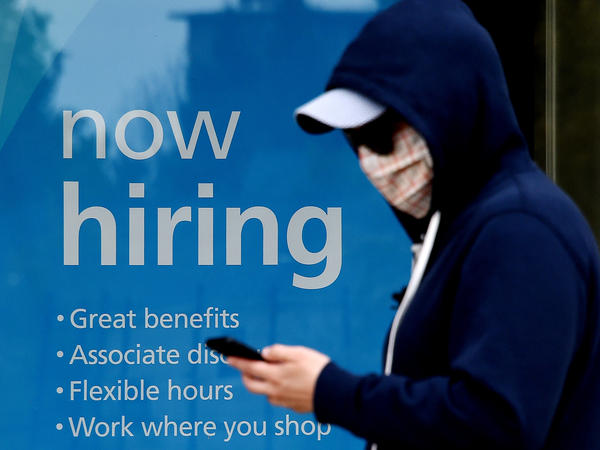 """Millions of gig workers have come to depend on a government lifeline that's set to expire at the end of the year. Above, a man wearing a face mask walks past a sign saying """"now hiring"""" on May 14 in Arlington, Va."""