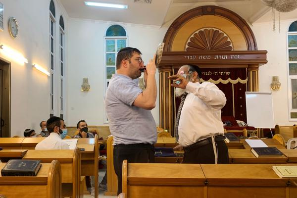 Rabbi Yehonatan Adouar (right) teaches a student during a shofar-blowing course in Rambam Synagogue in Ramat Gan, Israel.