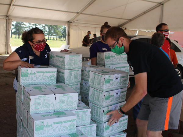 Each week, police in Lexington, Neb., cordon off several blocks near the edge of town, where roughly 700 cars will line up for USDA Farmers to Families food boxes. Above, volunteers organize boxes on Aug. 27, 2020.