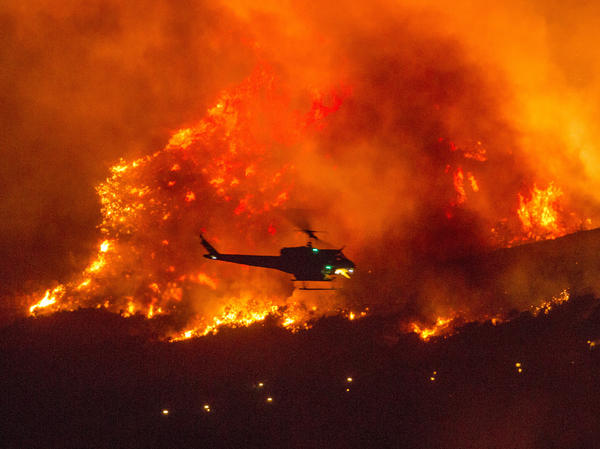 A helicopter prepares to drop water at a wildfire in Yucaipa, Calif., on Sept. 5. A firefighter was killed in the El Dorado blaze on Thursday.