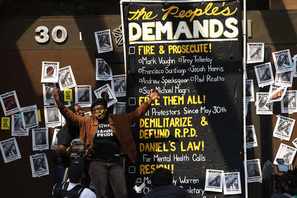 Activists Ashley Gantt, left, and Stanley Martin stand with a list of demands outside City Hall on Tuesday.