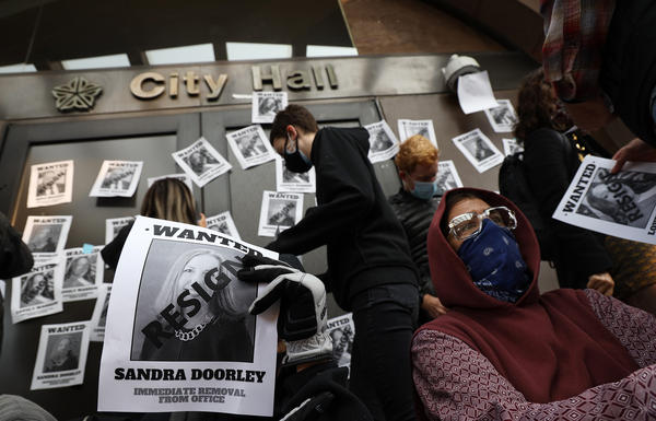 """Protesters paper the front of City Hall with """"wanted"""" posters calling for officials to resign and the officers involved in the Daniel Prude case to be fired and prosecuted."""
