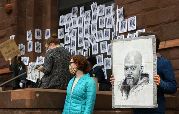 A protester holds a sketch of Daniel Prude during Tuesday's rally outside City Hall.