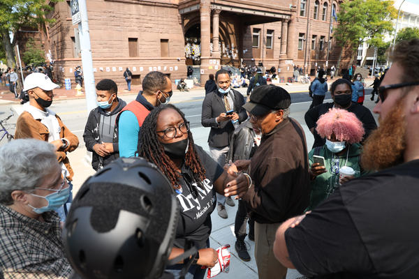 Ashley Gantt talks Tuesday to one of five men who came to the rally to oppose the U.S. flag being taken down in front of City Hall.