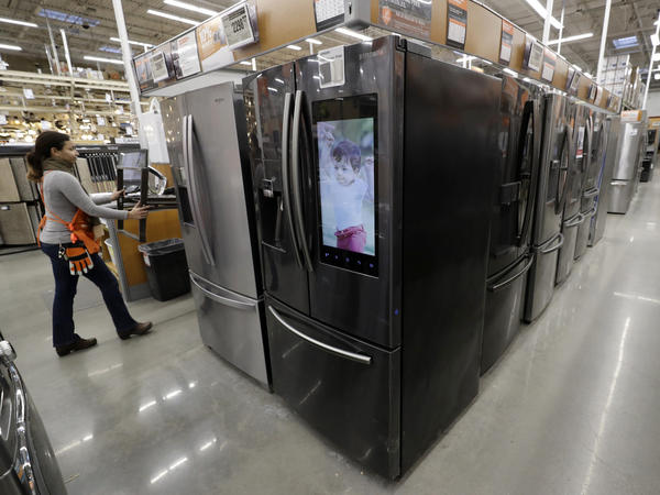 A worker pushes a cart past refrigerators at a Home Depot in Boston in January, before the coronavirus pandemic threw a monkey wrench into the supply and demand of major appliances.