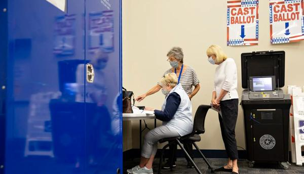 Connie Ford, back, assists Ann Massey, left, and Linda Frageman at a training lab at the Collin County Elections Department.