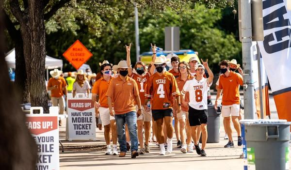 Fans walk toward the stadium for the first home football game of the season at the University of Texas at Austin. Students had to test negative for the coronavirus before attending the game.