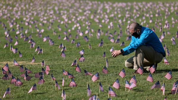 The U.S. hit a tragic milestone Tuesday, recording more than 200,000 coronavirus deaths. Here, Chris Duncan, whose 75-year-old mother, Constance, died from COVID-19 on her birthday, visits a COVID Memorial Project installation of 20,000 U.S. flags on the National Mall. The flags are on the grounds of the Washington Monument, facing the White House.