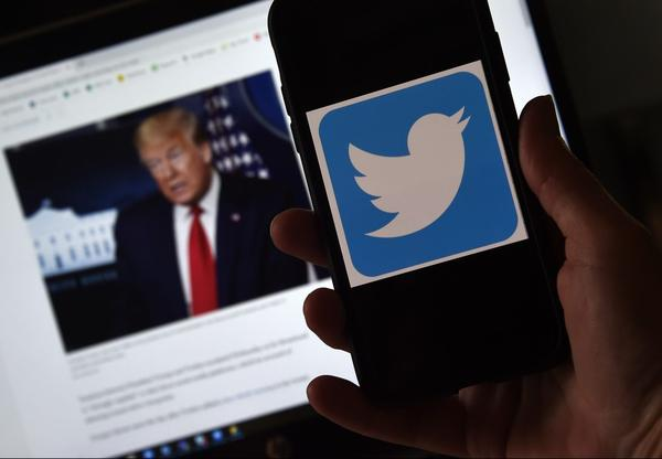 In this photo illustration, a Twitter logo is displayed on a mobile phone with a President Trump's picture shown in the background in Arlington, Virginia.