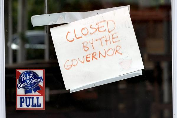 """A sign on the door of the West Alabama Icehouse reads """"Closed by the Governor"""", in June 2020, in Houston. Texas Gov. Greg Abbott shut down bars again and scaled back restaurant dining on Friday as cases climbed to record levels after the state embarked on one of America's fastest reopening."""