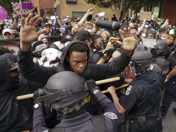 Police and protesters converge during a demonstration, Wednesday in Louisville, Ky. A grand jury has indicted one officer on criminal charges six months after Breonna Taylor was fatally shot by police in Kentucky.