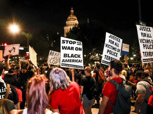 People protest the grand jury decision in the Breonna Taylor case in front of the Colorado state Capitol in Denver on Wednesday. As the protest was breaking up, a motorist drove through a small crowd of protesters who had yelled at the driver to turn around.