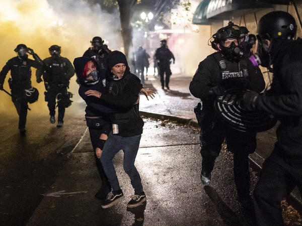 Protesters look for an escape while Portland police disperse a crowd in Portland, Ore. Wednesday. Violent protests erupted following the results of a grand jury investigation into the police shooting death of Breonna Taylor.