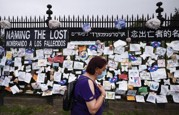 In this May 28, 2020, file photo, a woman passes a fence outside Brooklyn's Green-Wood Cemetery adorned with tributes to victims of COVID-19 in New York. The U.S. death toll from the coronavirus topped 200,000 Tuesday, Sept. 22, a figure unimaginable eight months ago when the scourge first reached the world's richest nation with its sparkling laboratories, top-flight scientists and towering stockpiles of medicines and emergency supplies. (Mark Lennihan/AP Photo File)
