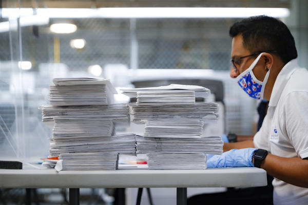 A worker prepares to check stacks of ballots in July at a Board of Elections facility in New York City. The city's election board says it will send about 100,000 new absentee ballots to voters after mailing out error-filled ones.