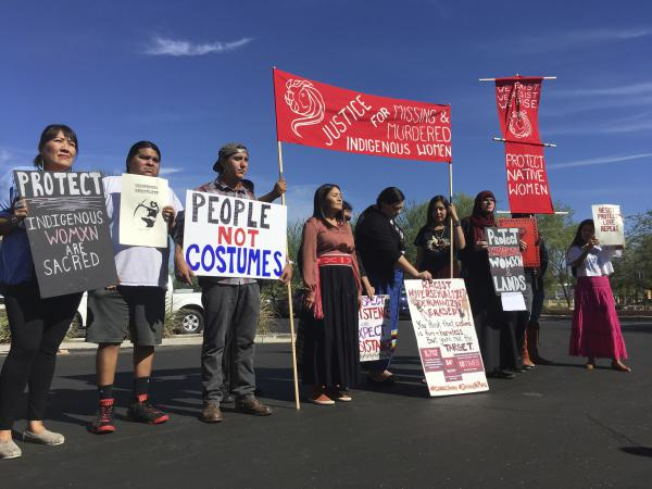 "Native American protesters stand outside the Phoenix office of a retailer of ""sexy Native American"" costumes last year. For some ethnic and racial groups, Halloween has long been haunted by costumes that perpetuate stereotypes and instances of cultural appropriation."