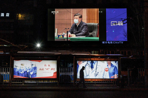 A large screen broadcasting an evening newscast along a Beijing street in March shows Chinese President Xi Jinping wearing a protective mask during his visit to Wuhan earlier in the day.