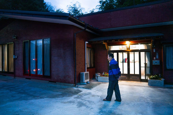 Shuichi Kanno, 79, walks in front of his home at dusk. Kanno has been dealing with hordes of macaque monkeys in his neighborhood in Japan. They frequently wake him up as they climb over his roof in the early morning hours.