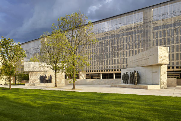 """The Dwight D. Eisenhower Memorial in Washington, D.C., will be dedicated on Thursday. A stainless steel, woven """"tapestry"""" made by artist Tomas Osinski stands behind the statues and depicts the cliffs at Normandy. Memorial design by Gehry Partners, sculpture by Sergey Eylanbekov and inscriptions by Nick Benson."""