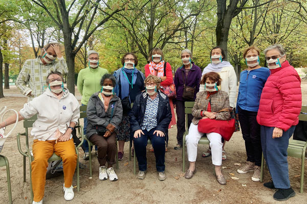 Suzy Margueron (seated, center) who advocates for people with hearing loss, likes to gather with friends in Paris' Luxembourg Gardens. All have transparent masks, but say it's others who should be wearing them too.
