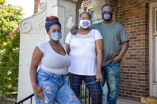 Heavenly Pettigrew, left, and her parents Stephanie and Robert outside their two-bedroom rental apartment in Milwaukee. Without assistance from the nonprofit Community Advocates, the family likely would have faced eviction after the pandemic forced Robert and Heavenly out of their steady jobs.