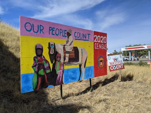 """A hand painted Census 2020 sign created by a local young artist in collaboration with Indigenous Creative Ben Pease, stands beside I-90 in Crow Agency. A """"Natives Count"""" sign created by Montana Native Vote stands beside it."""