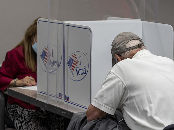 Voters cast ballots during early voting in Fairfax, Va., on Sept. 18, 2020. During the first presidential debate, President Trump would not commit to refraining from declaring victory until the election has been independently certified.